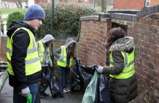 Students and staff picking up litter on a sloppy pathway near University of Worcester.