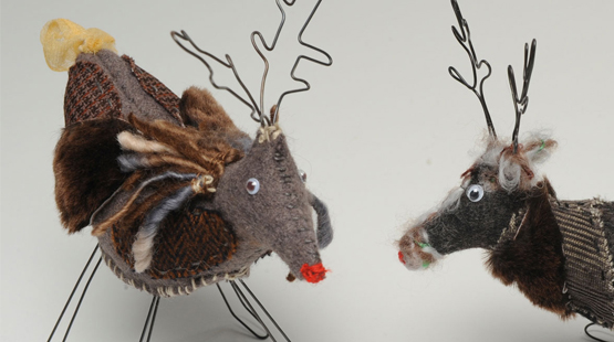 Two reindeer toys made from scrape material and wire on a white background.