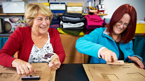 Two women stamping cardboard to be used as packaging.